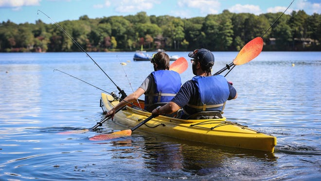 Miller Jacobus and his dad Andrew, of Sherborn, paddle out on the pond during the Fish for a Cause fishing derby at Farm Pond in Sherborn on Saturday.