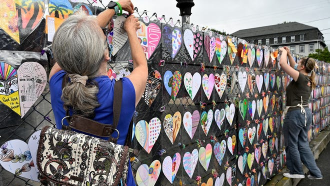 Volunteers Nancy Donahue, left, of Natick, and Diana Borshcheva help string up more than 1,000 handmade hearts for the Love 01760 public art installation Wednesday on the MBTA pedestrian bridge above the Natick Center commuter rail station. Since early May, Natick residents have been creating the hearts as a way of continuing community connections in spite of social distancing and sheltering in place due to the coronavirus pandemic.