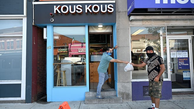 Ouahid Ouassaidi, owner of Kous-Kous, a Moroccan restaurant in downtown Framingham, hands lunch to a customer Friday.