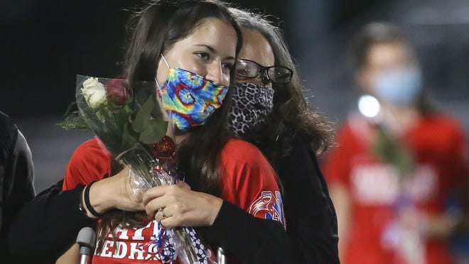 Natick's Kelly Pease gets a hug from her mom, Sandy, before a girls soccer game against Needham at Natick High School on Friday. Two days earlier, Pease broke her left ankle in a game.
