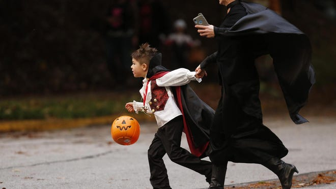 Locals and kids trick-or-treat along Boulevard in celebration of Halloween in Athens, Ga., on Thursday, Oct. 31, 2019.