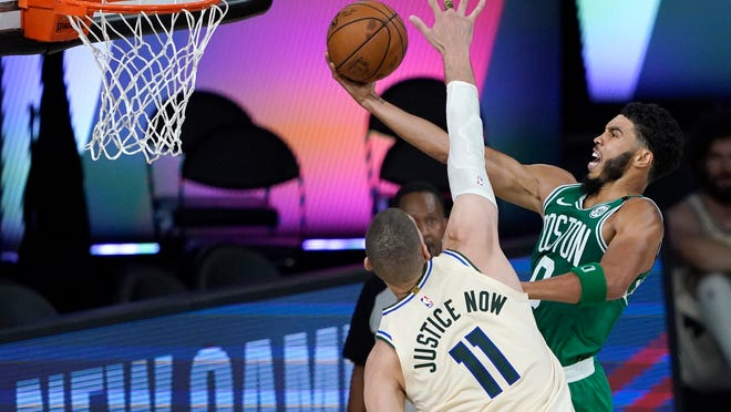 Boston Celtics' Jayson Tatum, right, heads to the basket as Milwaukee Bucks' Brook Lopez (11) defends during the first half of an NBA basketball game Friday, July 31, 2020, in Lake Buena Vista, Fla.