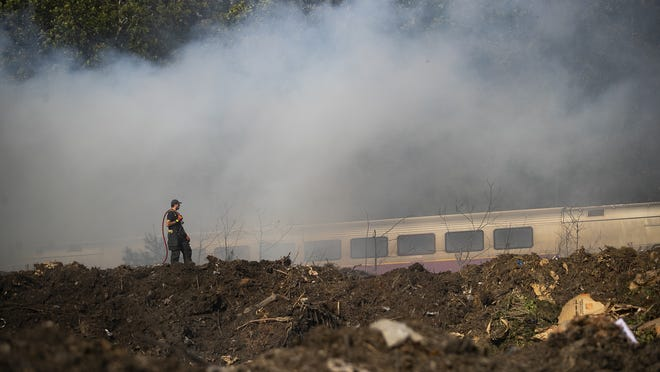 The commuter rail passes by as Brockton firefighters work to extinguish a mulch fire at 200 Oak Hill Way on Wednesday, Sept. 23, 2020.