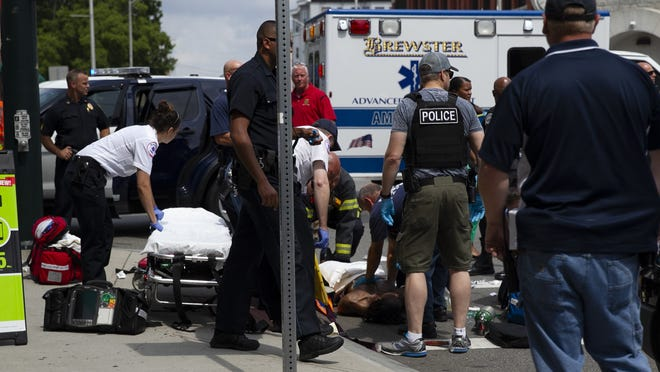 Brockton first responders treat a man with gunshot wounds on the scene at the corner of Pleasant and North Main St. on Wednesday, August 21, 2019. The suspect was transported to an area hospital.