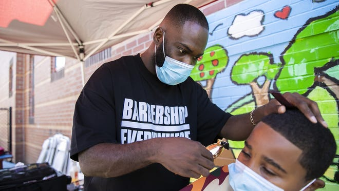 Marxmen Cuts barber Marc Amedee of Halifax gives Deliano Ribeiro, 8, a free haircut at the Look The Part For Remote Start event at the Arnone Elementary School in Brockton on Saturday, Sept. 26, 2020.