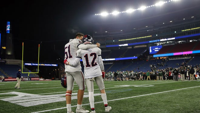 Lincoln-Sudbury's Will Ohler (left) and Nolan O'Brien talk as Mansfield players celebrate their win in the Division 2 Super Bowl at Gillette Stadium in Foxborough on Dec. 6, 2019. The football season this fall could be in jeopardy for high school football players.