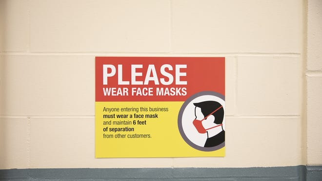 FILE - In this Tuesday, Sept. 15, 2020, file photo, a sign inside the Louise A. Conley Elementary School in Whitman reminds students and staff to wear face masks.