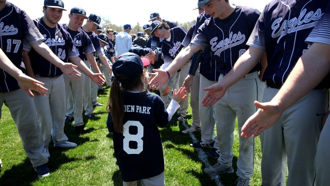 The Plymouth North baseball team high-five youth players as they come onto the field during Opening Day ceremonies for Plymouth Youth Baseball and Softball in 2017.