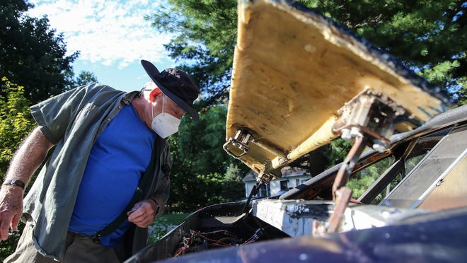 """Larry Brody checks the radiator of his hand-built car, which he calls an """"Arachnid,"""" Friday at his Holliston home. Brody is selling the vehicle for $6,000."""