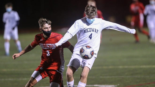 Medway's Alexander Morlock takes the ball from Holliston's Ryan Foley (left) during a boys soccer game at Holliston High School on Monday.