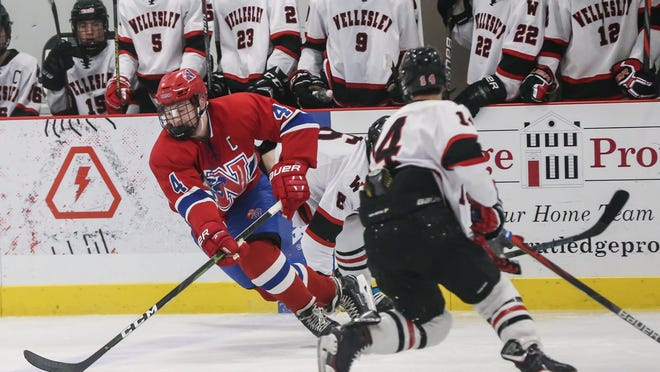 Natick's Max Gargurevich clears the puck during a Bay State Conference hockey game against Wellesley last season at the Boston Sports Institute in Wellesley. The Bay State Conference recently voted to delay the start of the winter sports season until at least Dec. 7.