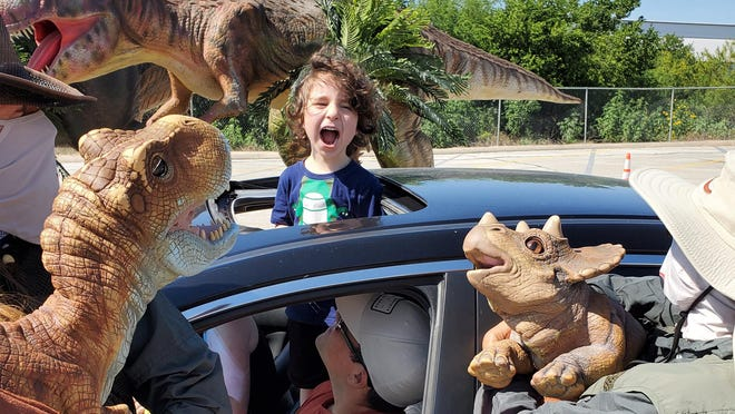 This promotional photo from June 13th, 2020 shows Jurassic Quest dinosaur puppeteers interacting with customers on the drive-through tour.