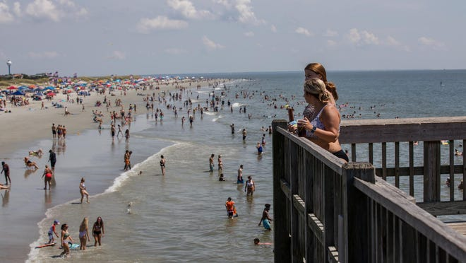Beach goers enjoy the sand, surf, and pier as they celebrate Independence Day Saturday on Tybee Island.