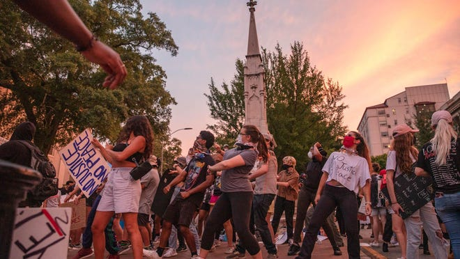 Athenians dance in front a Confederate memorial statue during a protest police brutality and the death of George Floyd, an unarmed black man who died in police custody last week, on Saturday, June 6, 2020, in downtown Athens, Georgia. A judge denied a Confederate heritage group's request for an order to prevent the Athens-Clarke County government from moving the memorial out of downtown Athens.