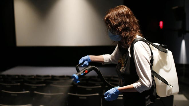 Bar manager Dottie Alexander disinfects theater one at Ciné in downtown Athens, Ga., on Wednesday, Oct. 14, 2020. The theater reopened last week for private screenings.