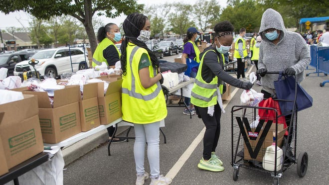 """The Rev. Cynthia Taylor, an Augusta Chronicle faith columnist, says there are countless ministry opportunities. """"For someone, somewhere - you are someone's answer to prayer,"""" she writes. Above, volunteers place groceries in Maria G.'s cart during a May 28 food distribution drive sponsored by Island Harvest Food Bank in Valley Stream, N.Y."""