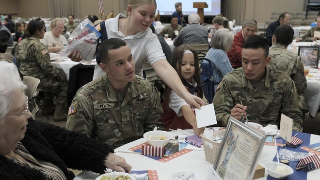 Maggie Voss, left, and Lily Koval of the American Heritage Girls Troop GA 1917 hand out hand written Veterans Day cards to troops from Fort Gordon at the Veterans Dinner at St. Teresa of Avila Catholic Church in Grovetown in this November 2019 file image. The Augusta metro area was recently named one of the best cities for active duty personnel transitioning to civilian life.