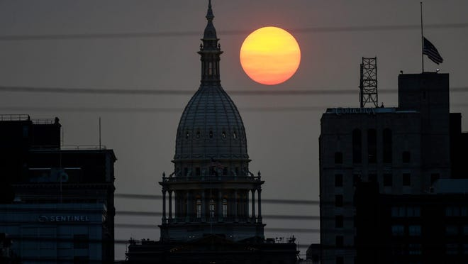 The sun sets behind the Michigan Capitol in downtown on Tuesday, Sept. 15, in Lansing. After bracing for possibly billions of dollars in cuts, state officials only had to cut about $250 million from state agency budgets because of reduced tax revenues resulting from the coronavirus pandemic.