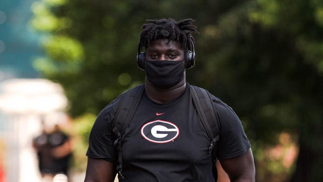 A UGA football player walks to a voluntary practice while wearing a mask on Thursday, July 23, 2020, in Athens, Georgia.