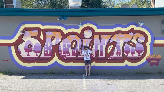 Artist Taylor Shaw poses with his recently completed Five Points mural on the side of Barberitos restaurant.