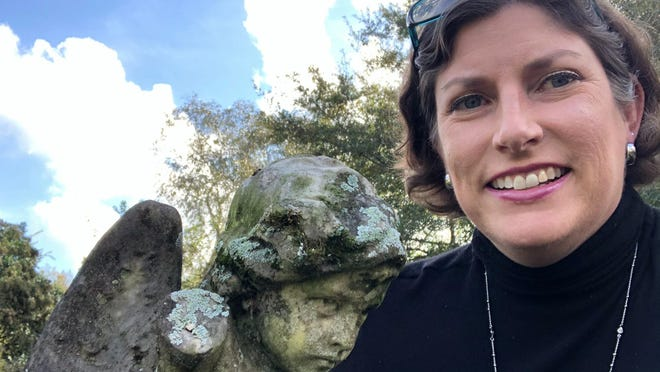 """In this photo from Oct. 24, 2020, """"Ghosts of Athens"""" author Tracy L. Adkins takes a selfie with the headstone that appears on the cover of her book at Oconee Hill Cemetery in Athens. Georgia."""