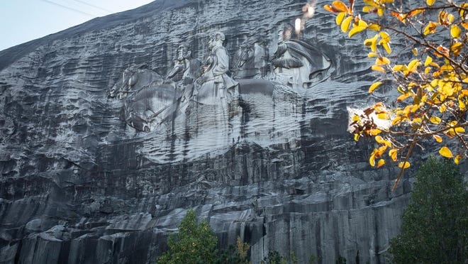 A massive mountainside carving depicting Confederate leaders Jefferson Davis, Robert E. Lee and Stonewall Jackson is shown on Monday, Oct. 5, 2020, in Stone Mountain, Ga. The grassroots group Stone Mountain Action Coalition is seeking to have the Confederate flag removed from the popular park and streets like Robert E. Lee Boulevard renamed there. They also want the park to allow the natural flora and fauna to grow over and obscure the carving.