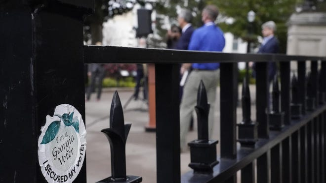 "A ""I'm a Georgia Voter sticker is seen on a fence as the Georgia Secretary of State Brad Raffensperger speaks during a news conference on Wednesday, Nov. 11, 2020, in Atlanta. Georgia election officials have announced an audit of presidential election results that will trigger a full hand recount."
