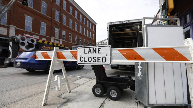 In this Tuesday, Aug. 6, 2019 photo, film crew close a lane on Pryor Street in downtown Atlanta to line equipment and trucks down the street. Georgia's economy benefits from $9.5 billion generated in the film industry each year.