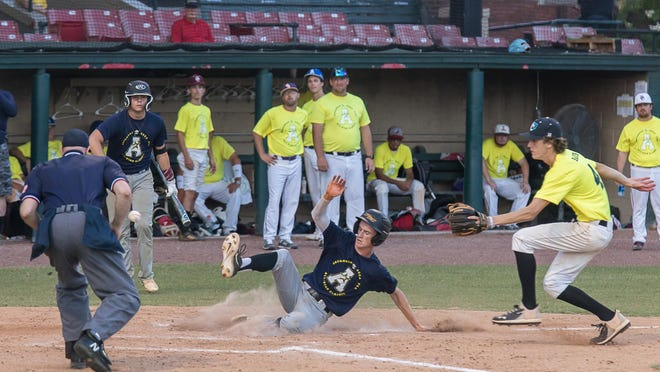 Richmond Hill's Mitch Cowan slides in for a score past Islands High's Pax Raub during Monday night's Savannah Area Fellowship of Christian Athletes All-Star Classic at Grayson Stadium.