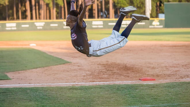 Savannah Bananas first base coach Maceo Harrison levitates in the air as he performs during a recent game at Grayson Stadium.