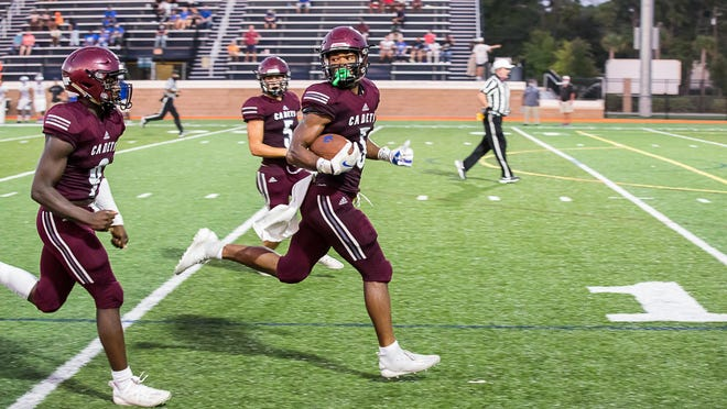 Benedictine's Trent Broadnax looks over his shoulder at teammate Lamont Mitchell as he sprints to the end zone for a touchdown on a 75-yard punt return during Friday night's season opener against Burke County.