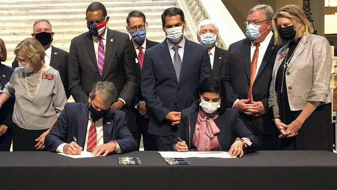 Georgia Gov. Brian Kemp and Centers for Medicare and Medicaid Services Administrator Seema Verma sign health care waivers at the state capitol in Atlanta on Thursday, October 15, 2020. Georgia's plans would provide Medicaid access to adults who make less than poverty level incomes who meet work requirements, and leave private brokers as the only avenue to buy federally-subsidized private insurance for people with above-poverty incomes.