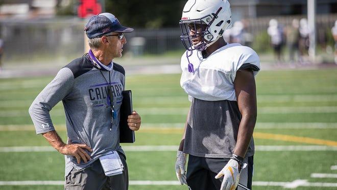 Calvary Day football coach Mark Stroud talks with running back Greg Daniel during practice earlier this season at Calvary Day School.