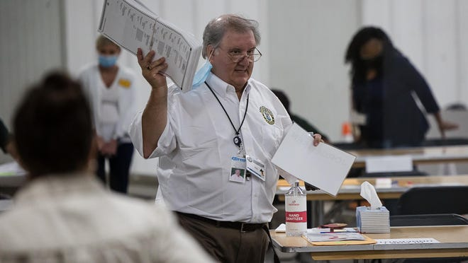 Chatham County Board of Elections Trainer Bill Wooten retrieves counted ballots from workers during the presidential election recount.
