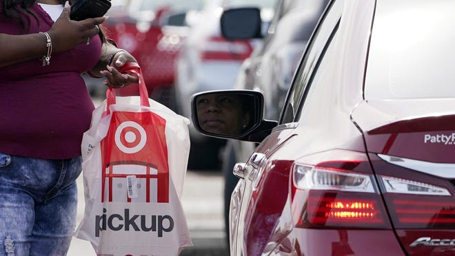 A Target employee prepares to hand a customer a curbside pickup purchase in Jackson, Mississippi on Nov. 5. Retailers and carriers are preparing for a holiday shipping surge that could mean delays in holiday gifts. Stores are pushing their customers to buy early to smooth out the peaks in the weeks leading up to Christmas. And they're further expanding services like curbside pickup to minimize online shipping.