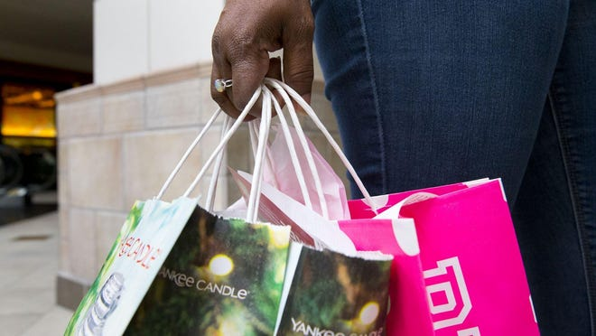 A shopper carries Black Friday finds following a 2018 shopping venture. This year, Black Friday at many stores will look a bit different from years past.