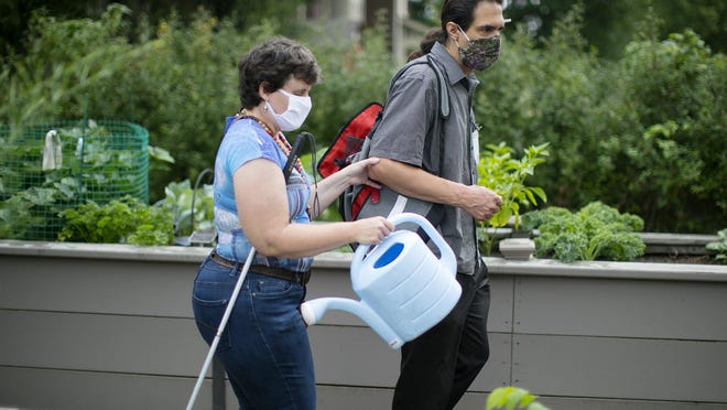 "Troy Dallman, with ARC Industries, helps Melanie Feeney to water a community garden plot at Franklin Park on Thursday, Aug. 27. Nonprofit agencies and companies that provide services to people with developmental disabilities have had a rough go the past several months. The state is helping with some ""relief"" payments to boost the agencies."