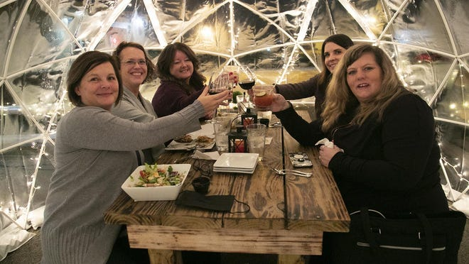 Vicki Coscarelli (left), Sharon Hawley (left-middle), Heather Hawley (left-back), Kim Foley (right-back) and Jewell Bryan (right) cheers during a meal inside the outdoor igloos at Danley's.