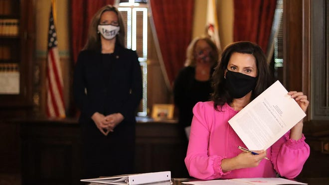 In this photo provided by the Michigan Office of the Governor, Gov. Gretchen Whitmer holds up Senate Bill 757 in Lansing, Mich., Tuesday, Oct. 6, 2020. The bill would allow clerks in certain cities or townships to begin processing absentee ballots prior to election day. It would also provide that clerks will notify voters of any reason their vote won't be counted within 48 hours.