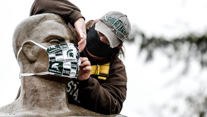 Michigan State University Infrastructure Planning and Facilities Landscape Services utility worker Kimberly Consavage adjusts a mask on the Sparty statute on Wednesday, April 22, 2020, on the Michigan State University campus in East Lansing. The mask was put on as a way to spread awareness in slowing the spread of the coronavirus.