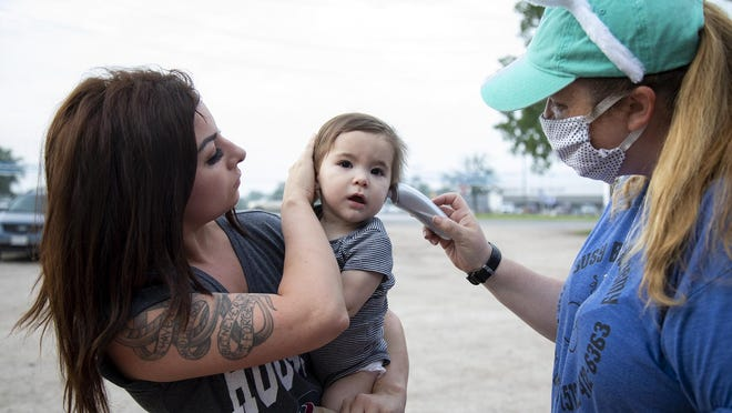 Kelsey Rutledge holds her daughter, Bonnie Ferguson, 20 months, as Sarah Smith, the owner of Busy Bee Academy, checks her temperature before she enters the daycare on April 9, 2020, in Bastrop, Texas.