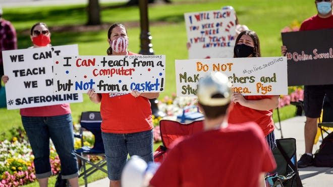 Participants hold up signs as Paul Sandy, a teacher from Pontiac, speaks during a rally on Thursday, Aug. 6, 2020, at the Capitol in Lansing. The event, organized by The Michigan Caucus Of Rank-and-File Educators (MI CORE), was held to call attention to the danger of schools physically reopening and demand more funding for protection.