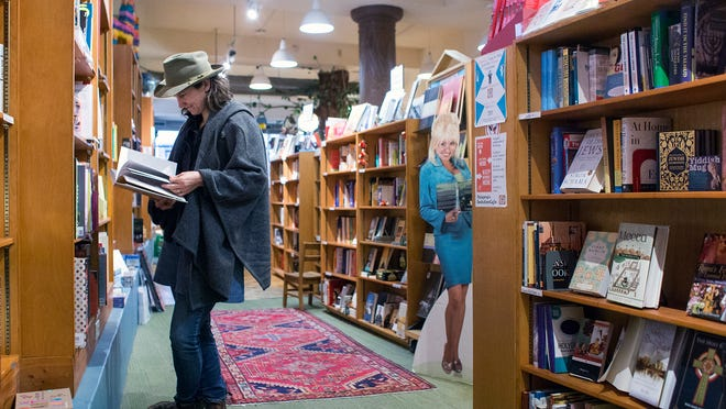 Rinne Allen, of Georgia, skims a book at Malaprop's on Monday. She said she always stops in at the independent downtown Asheville bookstore when she's in the city, because she likes looking at books she can't find in larger, chain stores.
