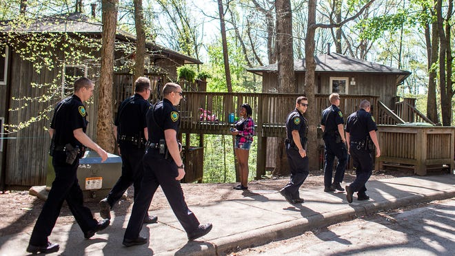 Members of the Asheville Police Department Housing Division walk through Klondyke Homes last week. Resident Quadaja Barr, 15, watches them go by. In an effort to improve safety and relationships within subsidized housing communities, APD is set to do a walk-through in one neighborhood every day.
