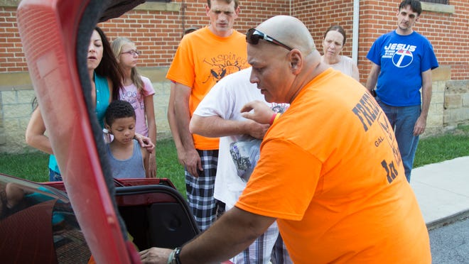 Volunteers from Father's Heart Healing Center help Donavan Harper unload donated supplies that will be handed out Saturday at the Blankets of Love event at the church.