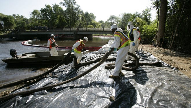 Workers pull oil-soaked  booms from the Kalamazoo River near Marshall on  on Aug. 6, 2010. Heavy black plastic is used to minimize contamination to the riverbank. A burst oil pipeline caused major environmental damage, prompting a more than $1-billion cleanup.