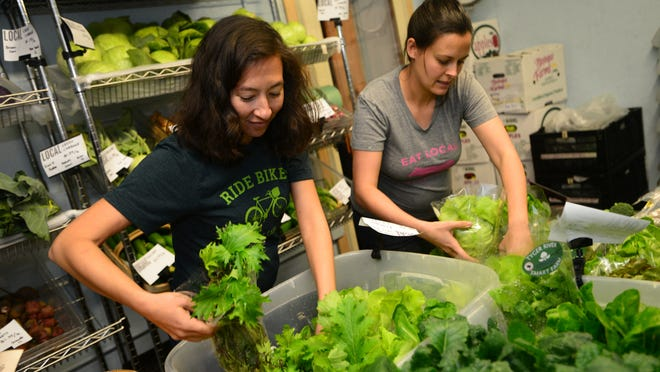Mary Walsh, left, and Jac Oliver package lettuce at Swamp Rabbit Cafe & Grocery, the business they opened in 2011 to focus on local food.