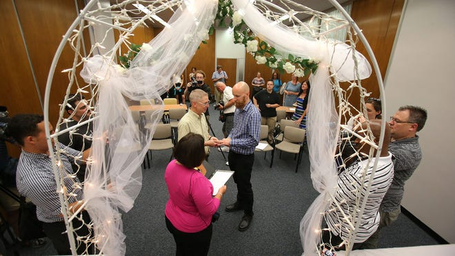 Bart Peterson (left) and Peter McNamara exchanged wedding vows in a wedding chapel set up at the City-County Building on Wednesday.