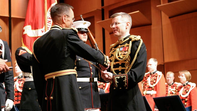 Marine Col. Timothy Foley (left) retires from the Marine Band and passes the baton to Lt. Col. Michael Colburn during a change of command concert on July 17, 2004, at the Schlesinger Concert Hall in Alexandria, Va.