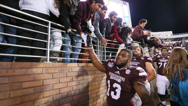 Mississippi State running back Josh Robinson celebrates the Bulldogs' 17-10 win over Arkansas with MSU fans.
